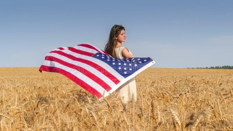 Muchacha hermosa con una bandera de los E.E.U.U. en el campo fotografía de archivo