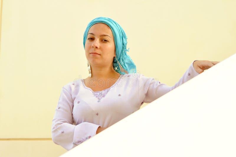 Muchacha hermosa con una bufanda en su cabeza abajo de las escaleras fotos de archivo