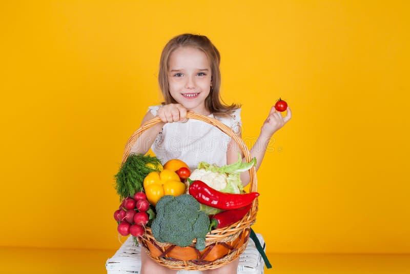 Muchacha hermosa con una cesta de verduras frescas, rábanos, bróculi, pimienta del tomate fotos de archivo
