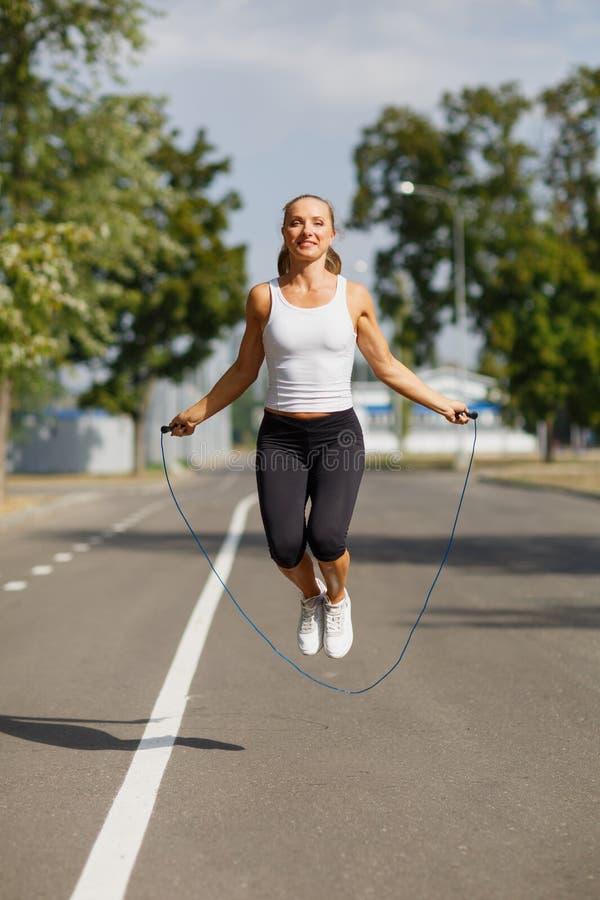 Muchacha hermosa con una cuerda de salto Se divierte a la mujer que salta en un fondo del parque Concepto activo de la forma de v fotografía de archivo libre de regalías