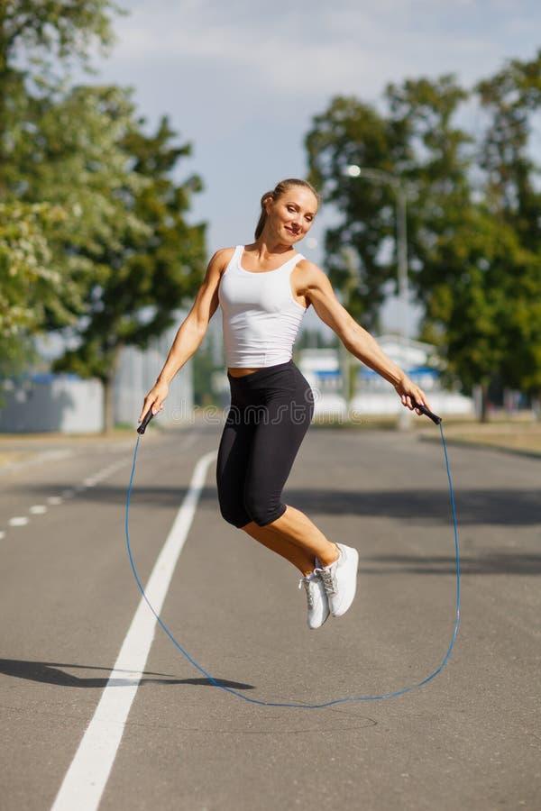 Muchacha hermosa con una cuerda de salto Se divierte a la mujer que salta en un fondo del parque Concepto activo de la forma de v fotos de archivo