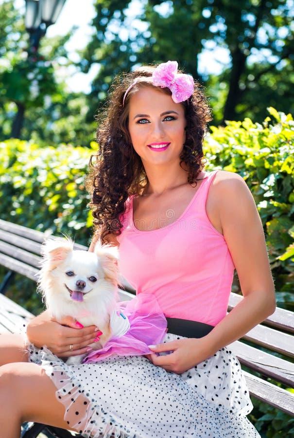 Muchacha hermosa con una pequeña chihuahua del perro en el parque fotografía de archivo libre de regalías