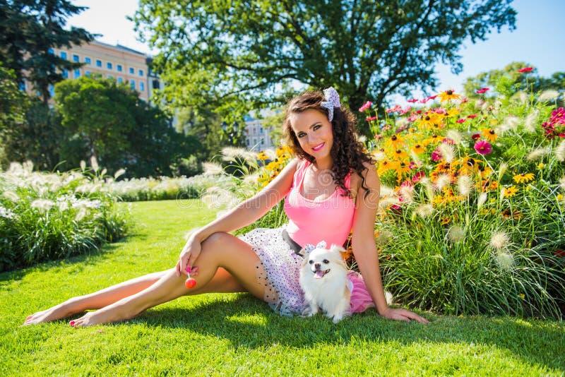 Muchacha hermosa con una pequeña chihuahua del perro en el parque imagen de archivo libre de regalías