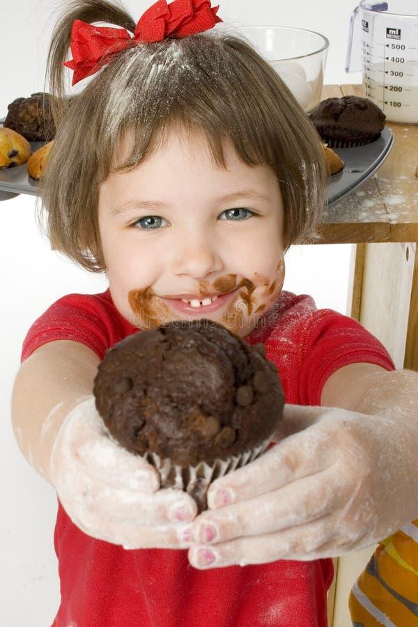 Muchacha hermosa de cuatro años con el mollete de la viruta de chocolate fotos de archivo