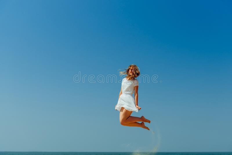 Muchacha hermosa de Joyfull que salta en la playa Vacaciones y relajaci?n imagenes de archivo