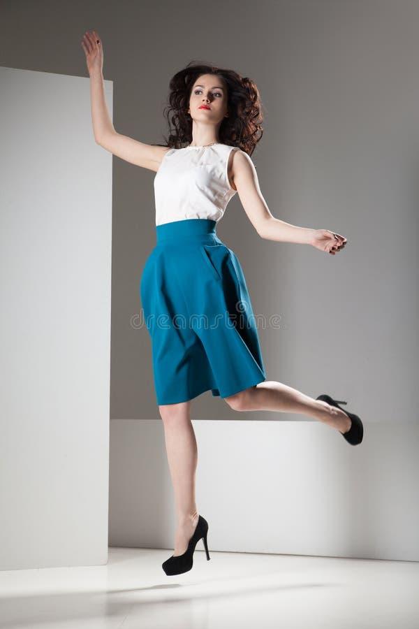 Muchacha hermosa de la moda en la falda azul marino que salta en fondo gris y blanco foto de archivo libre de regalías
