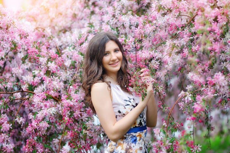 Muchacha hermosa de la moda en un jardín de flores imagen de archivo libre de regalías