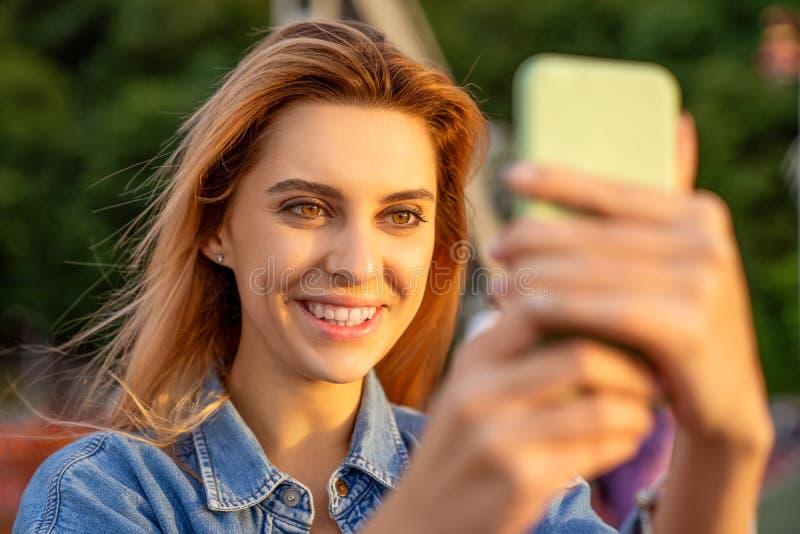 Muchacha hermosa de la moda que hace el selfie con el teléfono en la puesta del sol imagen de archivo