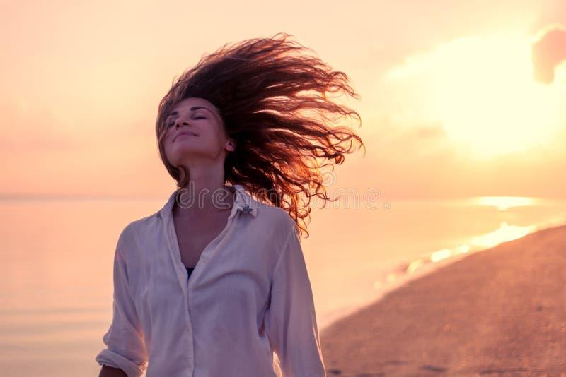 Muchacha hermosa de la mujer joven con el pelo rizado del vuelo en el fondo de una playa tropical en la puesta del sol, belleza,  imágenes de archivo libres de regalías