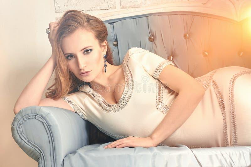 Muchacha hermosa de la mujer joven que miente en el sofá fotografía de archivo