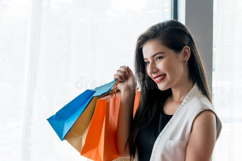 Muchacha hermosa de la sonrisa que sostiene el panier colorido imágenes de archivo libres de regalías
