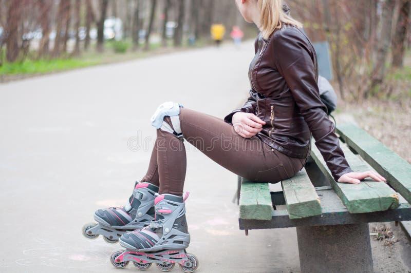 Muchacha hermosa de los pies de los scates del rodillo al aire libre fotografía de archivo