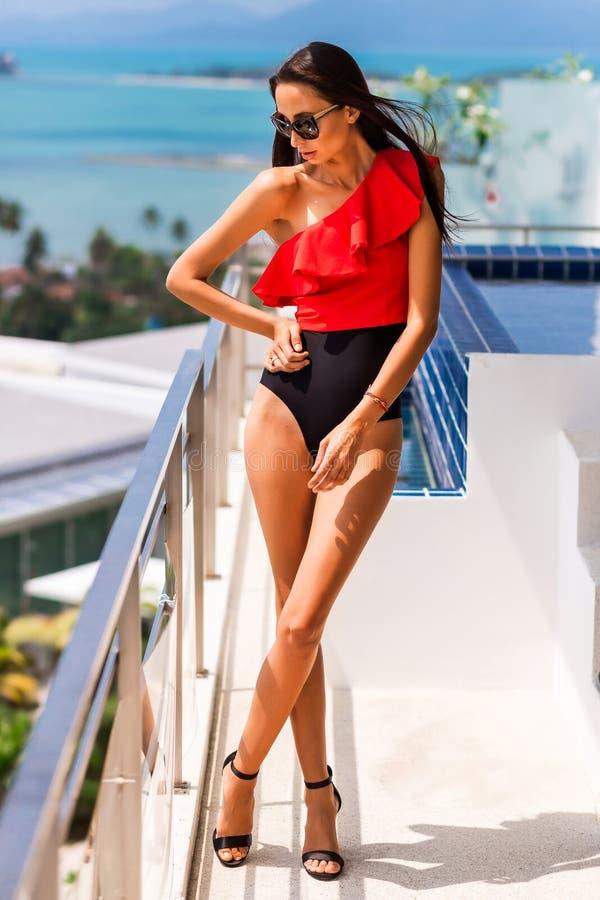 Muchacha hermosa de lujo en un traje de baño calificado y vidrios, en un hotel costoso en una isla tropical, contra un fondo del  fotografía de archivo