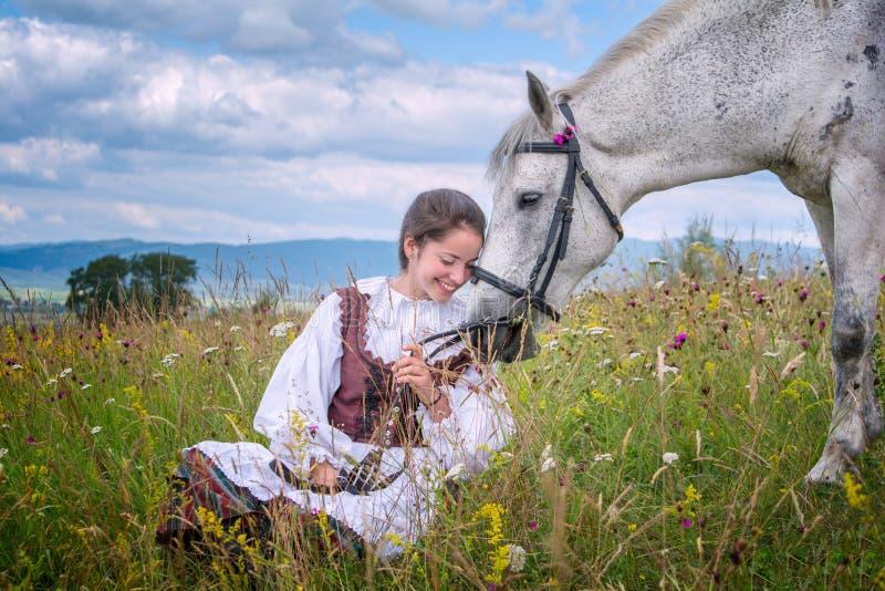 Muchacha hermosa de Rumania y traje tradicional en tiempo de verano y caballo árabe hermoso fotografía de archivo libre de regalías