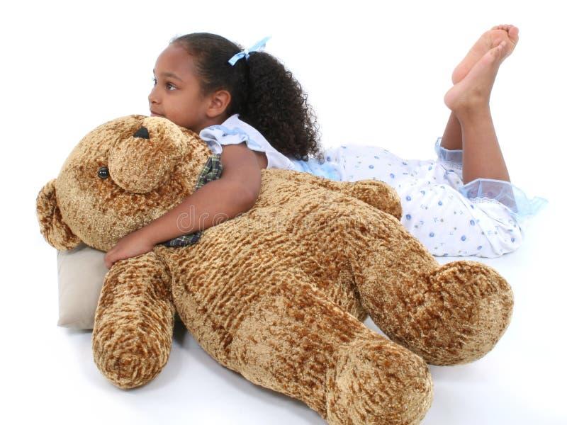 Muchacha hermosa de seis años que coloca en pijamas con el oso imagen de archivo