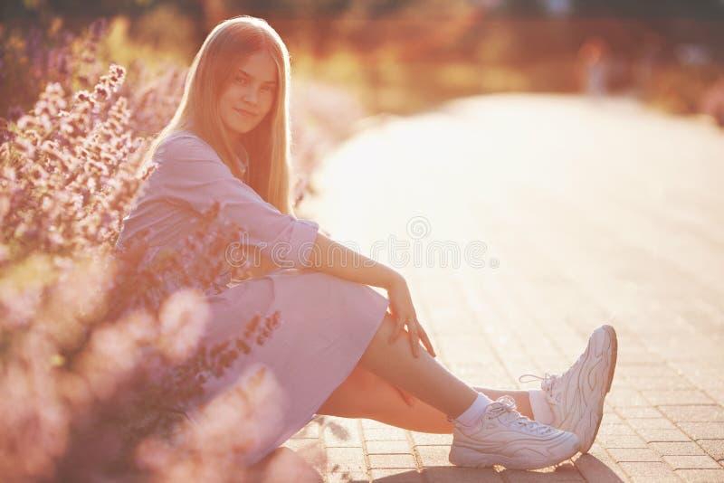 Muchacha hermosa del adolescente que se sienta al aire libre en flores y que mira la cámara foto de archivo