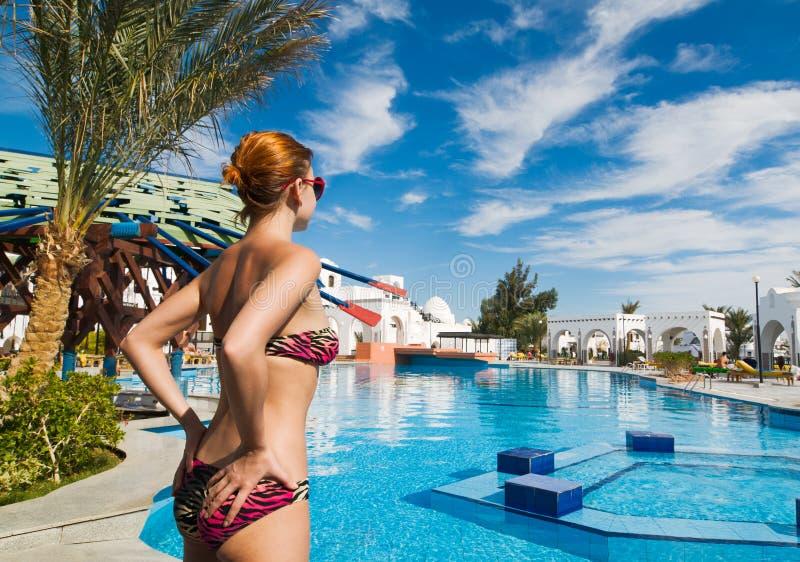 Muchacha hermosa del bikiní al lado de una piscina foto de archivo libre de regalías