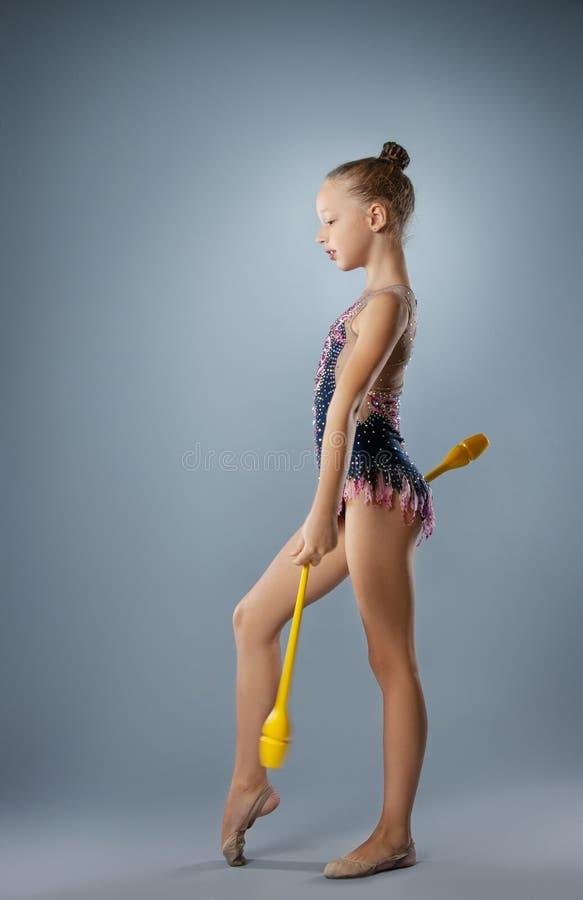 Muchacha hermosa del gimnasta en la ropa de deportes, elemento de la gimnasia rítmica con macis en fondo gris fotos de archivo