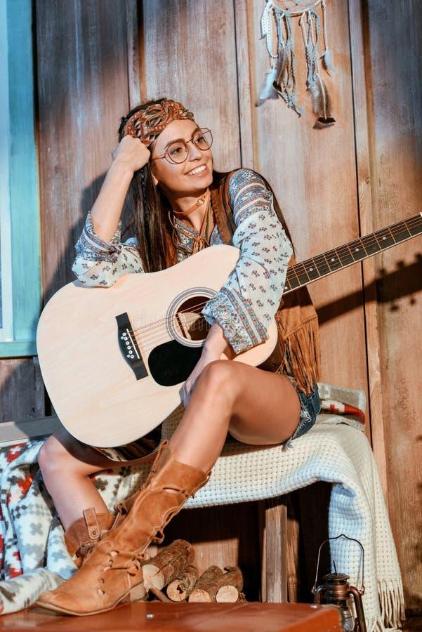 Muchacha hermosa del hippie en la venda y los vidrios que se sientan con una guitarra foto de archivo
