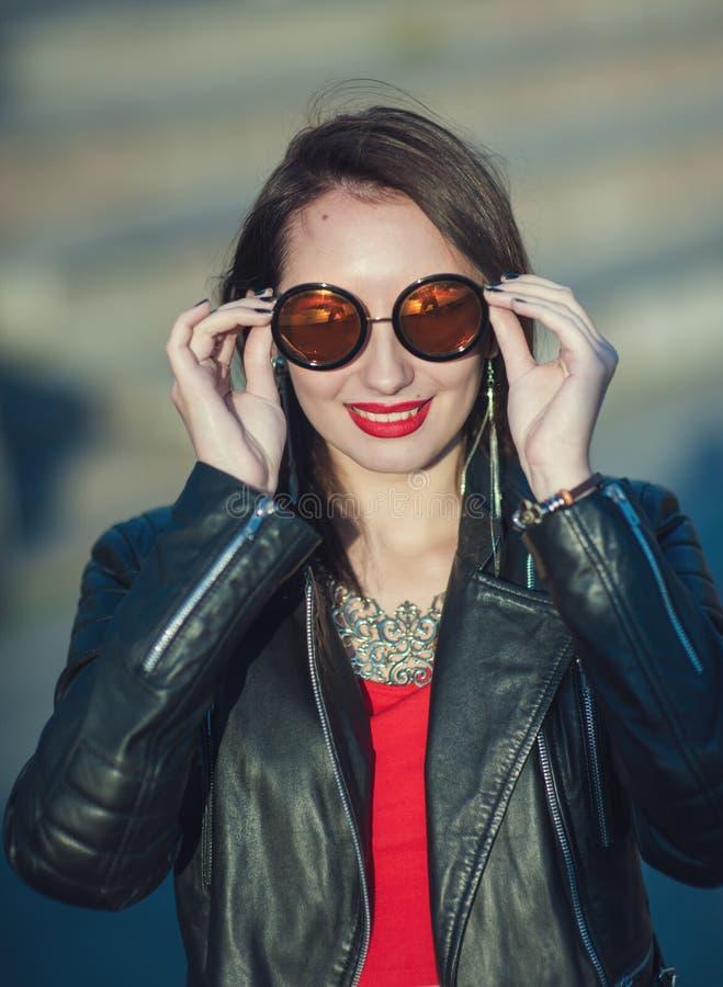 Muchacha hermosa del inconformista joven de la moda en la chaqueta de cuero y gafas de sol fotografía de archivo libre de regalías