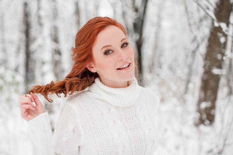 Muchacha hermosa del jengibre en el suéter blanco en la nieve diciembre del bosque del invierno en parque Tiempo de la Navidad fotos de archivo