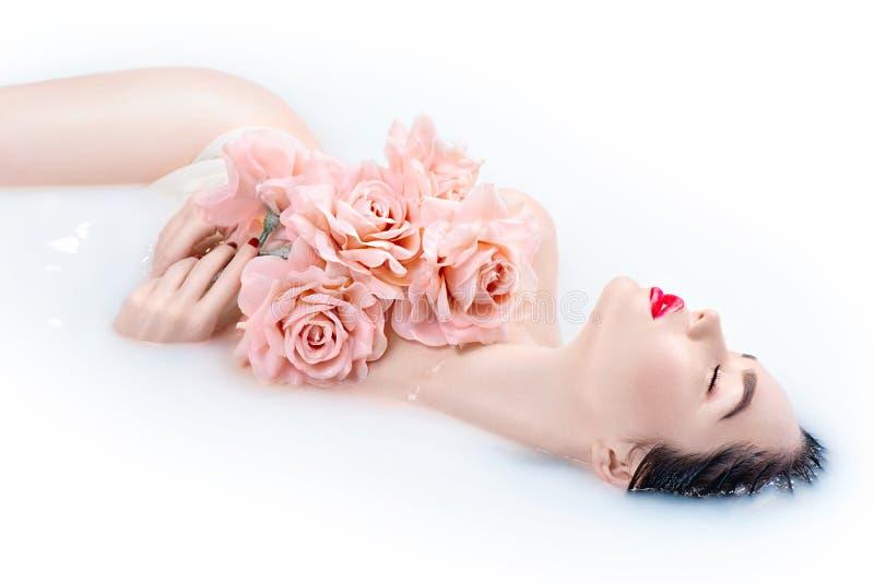 Muchacha hermosa del modelo de moda con maquillaje brillante y rosas rosadas que toman el baño de la leche foto de archivo