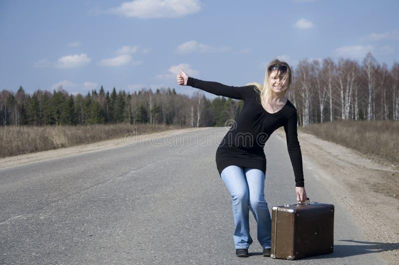 Muchacha hermosa del país que hace autostop en el camino foto de archivo