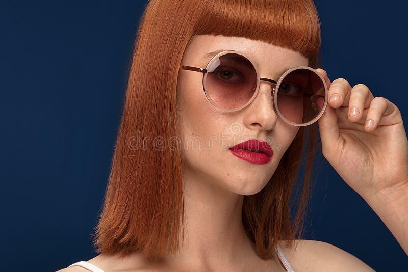 Muchacha hermosa del pelirrojo en gafas de sol en fondo azul fotos de archivo
