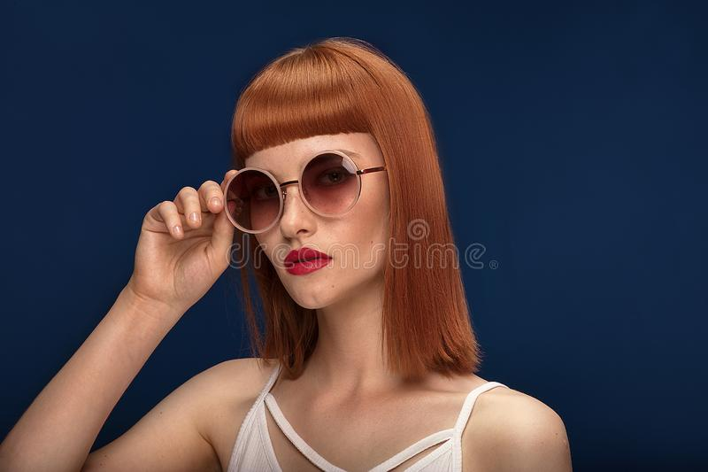 Muchacha hermosa del pelirrojo en gafas de sol en fondo azul imagenes de archivo