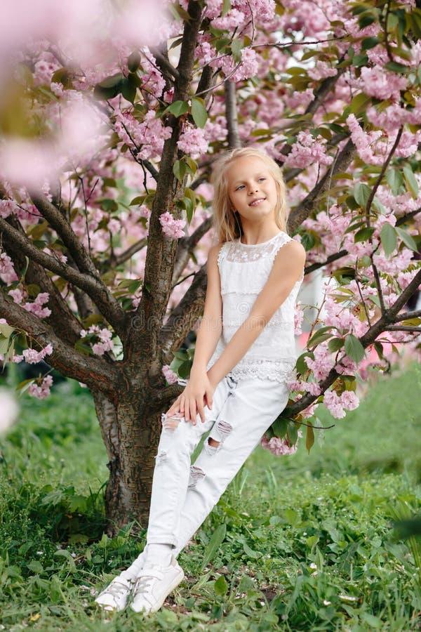 Muchacha hermosa del peque?o ni?o con las flores de Sakura fotos de archivo