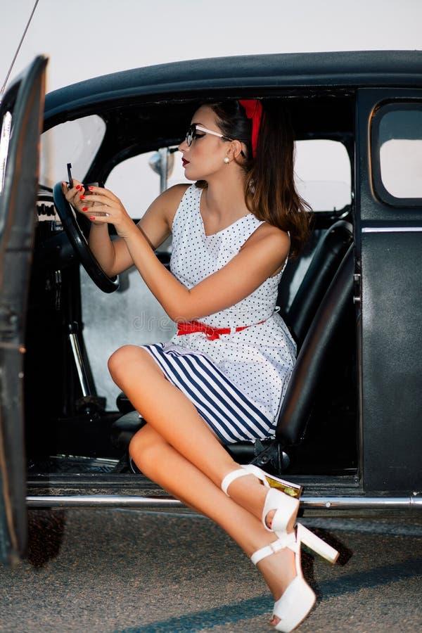Muchacha hermosa del perno-para arriba dentro del espejo de observación del coche del vintage foto de archivo