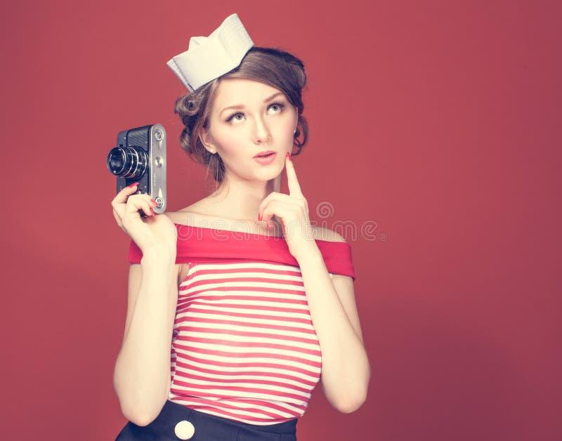 Muchacha hermosa del perno-para arriba que lleva a cabo en la suya la mano una cámara del vintage fotos de archivo libres de regalías