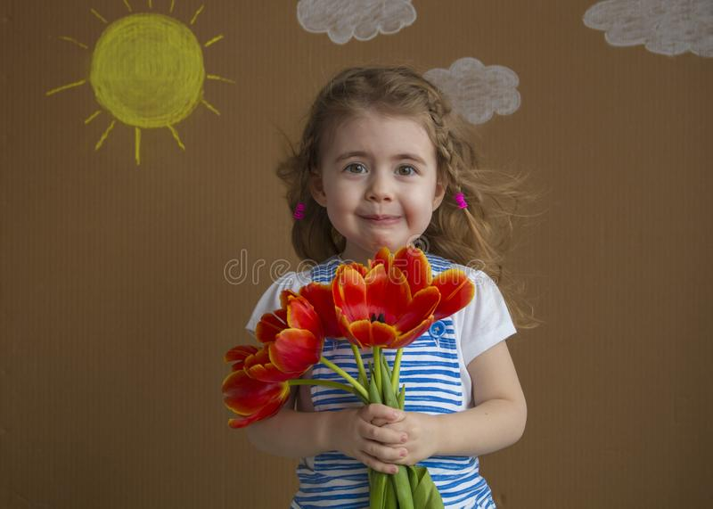 Muchacha hermosa del retrato emocional en el vestido azul con los tulipanes de las flores en manos en un fondo ligero con el sol  imagenes de archivo