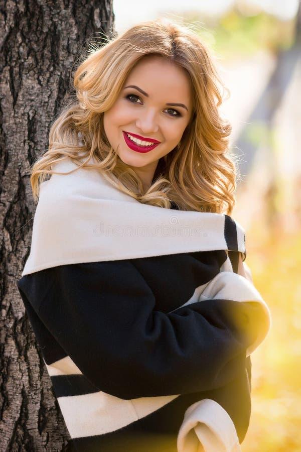 Muchacha hermosa del retrato que sonríe mientras que camina en el bosque imagen de archivo