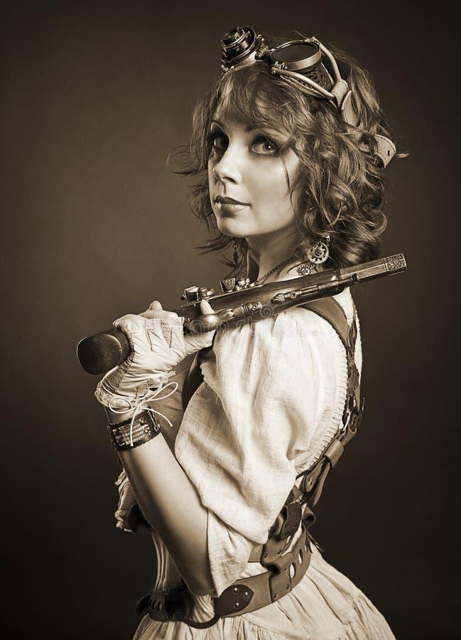 Muchacha hermosa del steampunk del redhair con el arma que mira la cámara viejo fotos de archivo libres de regalías