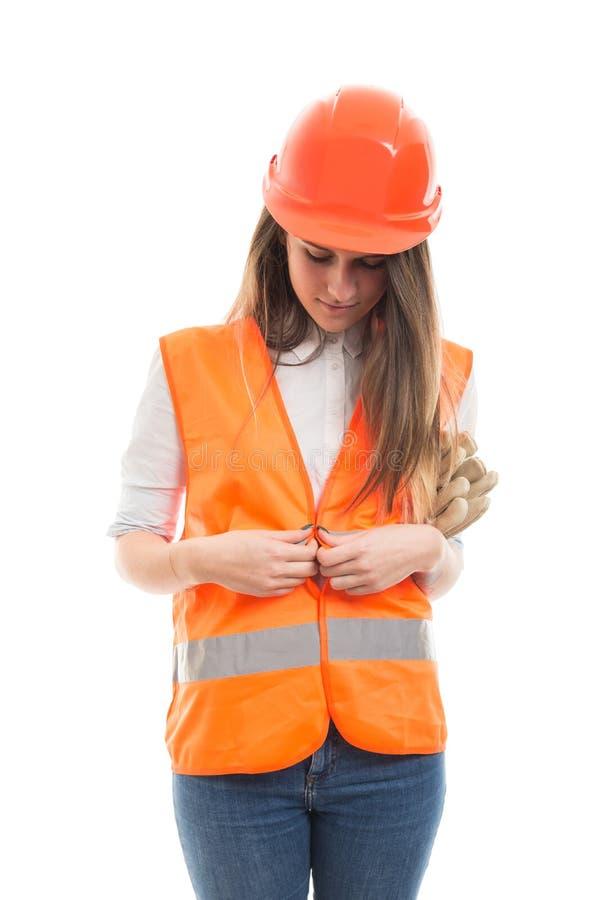 Muchacha hermosa del trabajador de construcción que abotona su chaleco imagen de archivo libre de regalías