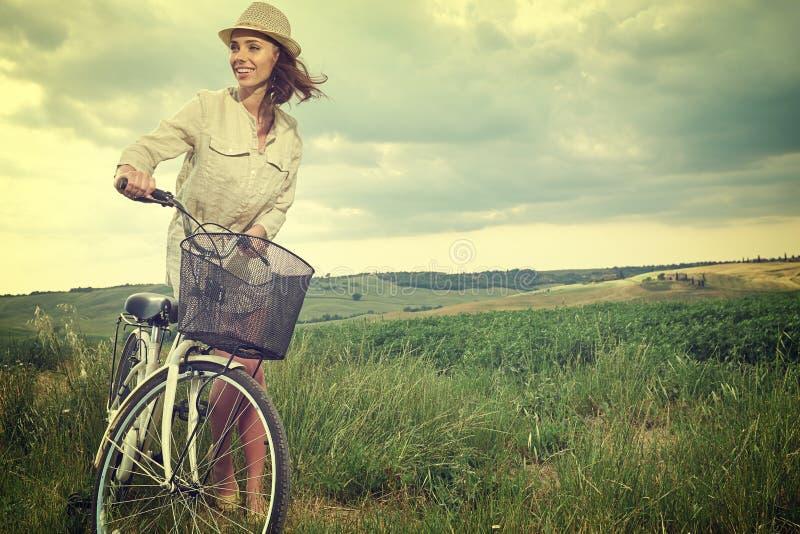 Muchacha hermosa del vintage que se sienta al lado de la bici, tiempo de verano fotos de archivo libres de regalías