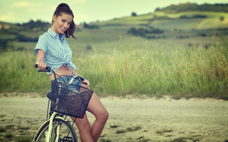 Muchacha hermosa del vintage que se sienta al lado de la bici, tiempo de verano fotos de archivo