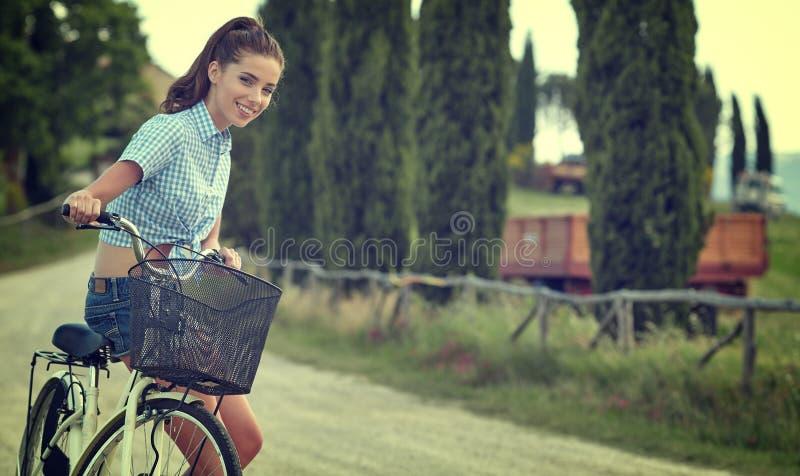 Muchacha hermosa del vintage que se sienta al lado de la bici, tiempo de verano foto de archivo