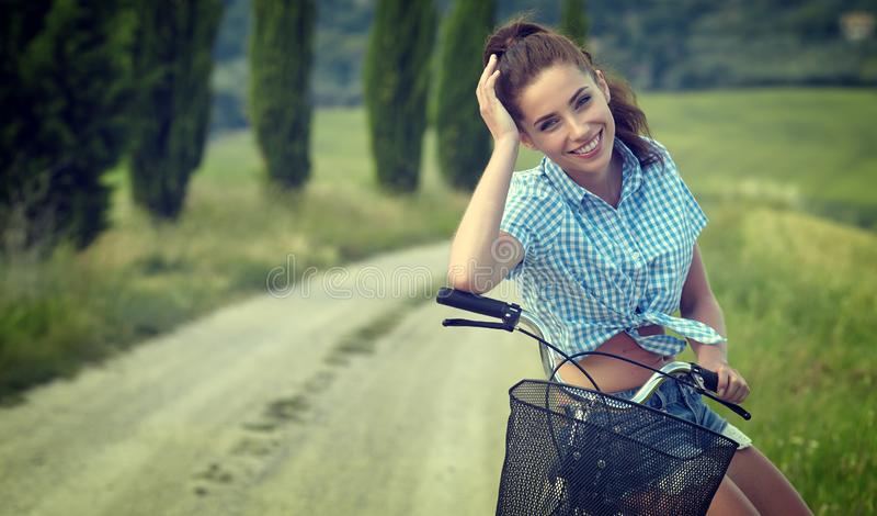 Muchacha hermosa del vintage que se sienta al lado de la bici, tiempo de verano foto de archivo libre de regalías