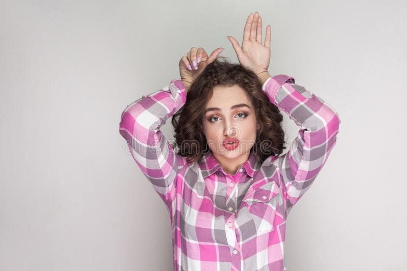 Muchacha hermosa divertida con la camisa a cuadros rosada, peinado rizado imagen de archivo