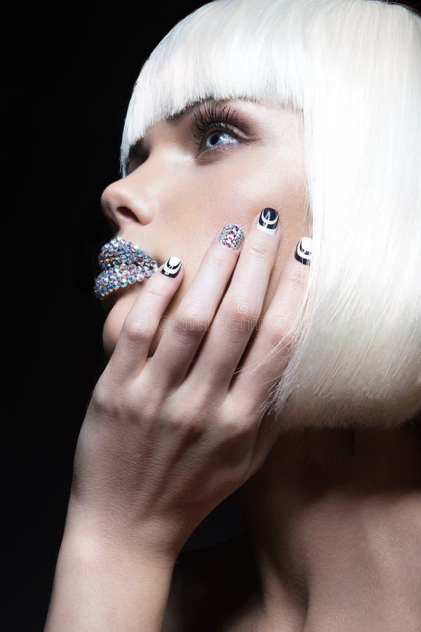 Muchacha hermosa elegante en una peluca blanca, con los labios de diamantes artificiales y de la manicura festiva Cara de la bell fotos de archivo