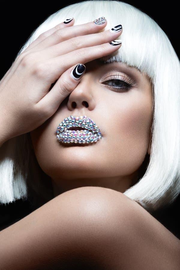 Muchacha hermosa elegante en una peluca blanca, con los labios de diamantes artificiales y de la manicura festiva Cara de la bell imagenes de archivo