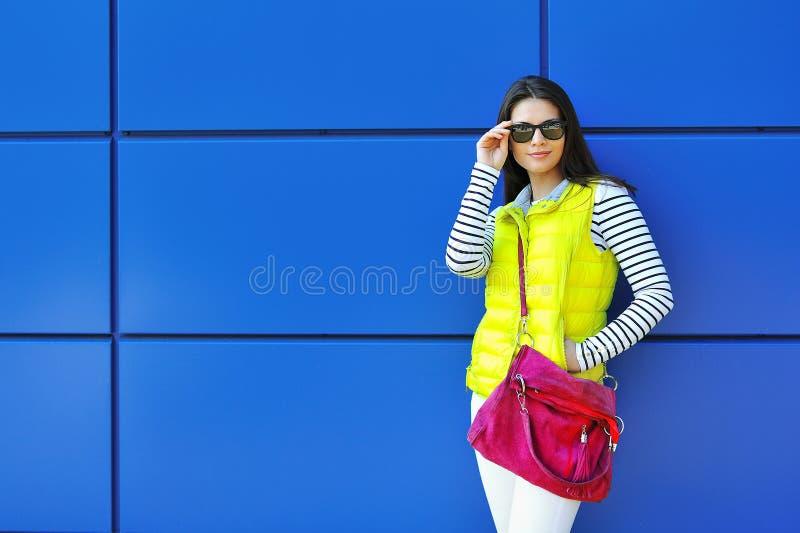 Muchacha hermosa elegante que se coloca cerca de la pared azul fotos de archivo libres de regalías