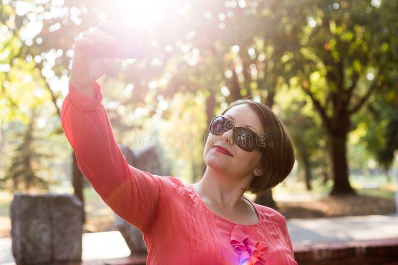 Muchacha hermosa en blusa rosada que sonríe y que toma Selfie en un parque imagen de archivo libre de regalías