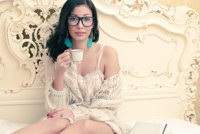 Muchacha hermosa en café de consumición de las gafas de moda fotografía de archivo