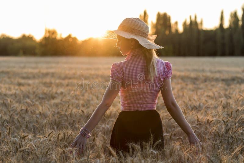 Muchacha hermosa en caminar a través de campo de trigo fotografía de archivo libre de regalías
