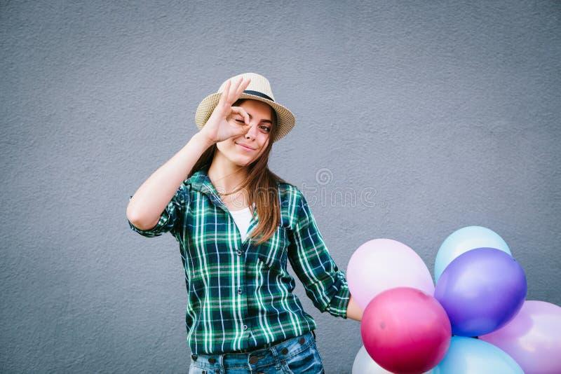 Muchacha hermosa en camisa y sombrero de tela escocesa con los globos que hacen la diversión y la sonrisa fotografía de archivo