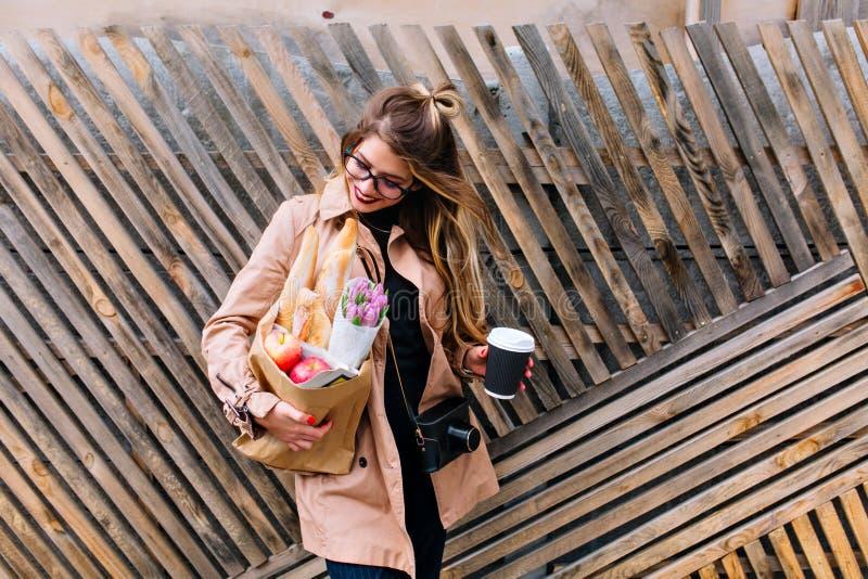 Muchacha hermosa en devoluciones de los vidrios de la tienda que sostiene una bolsa de papel con la comida y las flores Mujer jov foto de archivo