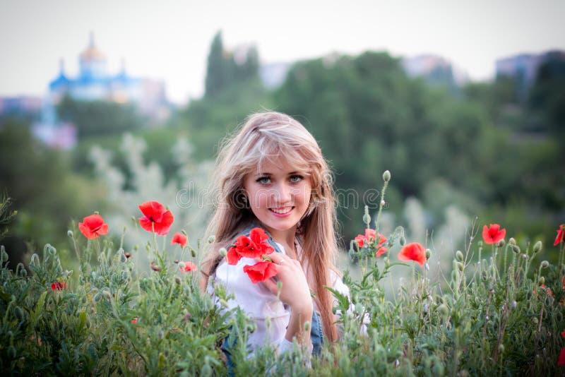 Muchacha hermosa en el campo con las amapolas imagen de archivo libre de regalías